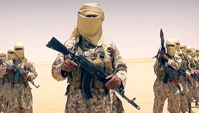 Image of foreign soldier with a full beige headscarf standing amongst other similar soldiers, holding a semi-automatic weapon.