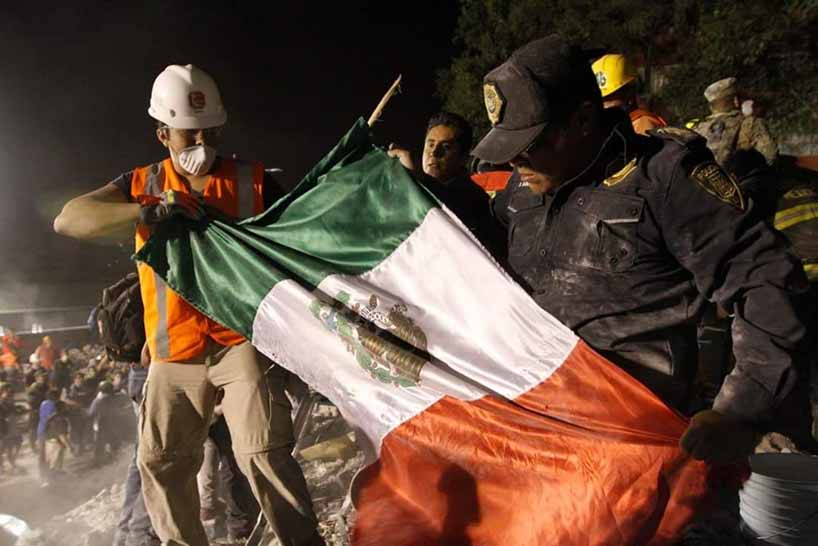Rescue workers unfurling Mexican flag.